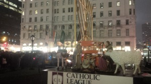 Manger scene for the Catholic League charities in front of the Chanukiah with the Plaza Hotel in the background.